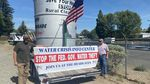"""Two men hold a sign that reads """"stop the Fed. Gov. water theft."""""""