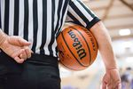 A referee holds the ball in the quarterfinals of the OSAA 6A Boys Basketball Championships between Grant High School and West Salem High School at the Chiles Center in Portland, Oregon, Thursday, March 8, 2018.