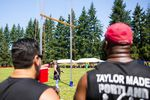 Throwers watch a fellow competitor.