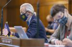 A lawmaker wearing a face mask is seen in focus from the site sitting at a desk on the Oregon Senate floor. Other people are also at desks, but out of focus.