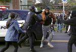 Police push a protester outside the Red House in North Portland, Ore., where a group of people attempted to stop an eviction process, Tuesday, Dec. 8, 2020.