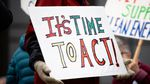 """A close up of a protester's sign, which reads """"It's time to act!"""" in bright colors."""
