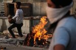 Family members cremate the body of a person who died after contracting COVID-19 in New Delhi, India, on Monday.