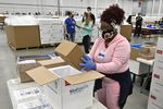 An employee with the McKesson Corporation packs a box of the Johnson and Johnson COVID-19 vaccine into a cooler for shipping from their facility in Shepherdsville, Ky., Monday, March 1, 2021.