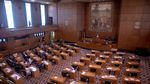 The floor of the Oregon House of Representatives shows desks aligned in rows facing other desks and a podium.