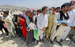 """A man holds a certificate acknowledging his work for Americans as hundreds of people gather outside the international airport in Kabul, Afghanistan, Tuesday, Aug. 17, 2021. The Taliban declared an """"amnesty"""" across Afghanistan and urged women to join their government Tuesday, seeking to convince a wary population that they have changed a day after deadly chaos gripped the main airport as desperate crowds tried to flee the country. (AP Photo)"""