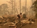 Sam Drevo walks through wildfire damage in September 2020 in the town of Gates, Ore., where he owned a home and river guide business.