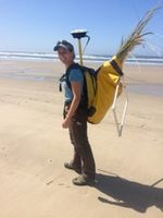 A woman standing on the beach smiling while carrying a backpack filled with beachgrass cuttings and scientific research equipment.