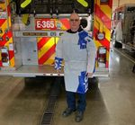 Firefighter Jim Wilson models a protective gown he made out of construction-grade vapor barrier.