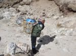 A porter carries a barrel of human waste from Mount Everest base camp to the small village of Gorak Shep.