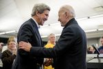 In this Feb. 1, 2020, file photo Democratic presidential candidate former Vice President Joe Biden smiles as former Secretary of State John Kerry, left, takes the podium to speak at a campaign stop at the South Slope Community Center in North Liberty, Iowa.