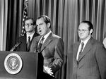 A black-and-white photo shows former President Richard Nixon speaking at a podium flanked by two men in suits with a US flag in the background.