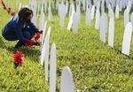 Mary Estime-Irvin, a councilwoman for the city of North Miami, writes the name of a friend lost to COVID-19 on a symbolic tombstone that is part of a pandemic memorial at Griffing Park in North Miami on Oct. 28, 2020.