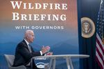 """Joe Biden sits at a table. Behind him, a wall-sized sign reads """"Wildfire briefing with governors"""""""