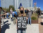 """A young woman wearing a facemask looks into the camera while holding a sign with the message, """"DOES IT WEIGH ON YOU AT ALL?"""" Behind her are several people and an office building."""