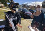 Two canvassers stand on a sidewalk talking with a person off camera who is holding a cellphone. One canvasser is wearing a Biden face mask, a visor and sunglasses while gesturing to informational placards she's holding. The other holds her phone in her right hand as she listens.