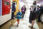 Gov. Kate Brown (center right, dark blue mask) visits  Scott Elementary School in Northeast Portland on  April 1, 2021. Arrows and lines on the floor tell students and staff how to walk down the school halls to maintain distance.