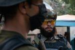 A Taliban guard (right) stands adjacent to a Pakistani guard on the Torkham border.