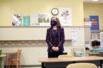 A woman wearing a mask and a business suit clasps her hands together while standing in an empty grade-school classroom.