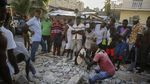 People gather around a mound of rubble as a man uses a stone to dig through the rocks.