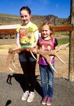 Kyra and Bobbi Cline, 11 and 7, hold up an elk antler they found.