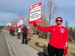 """People stand in a line outside a hospital, holding up signs that read """"OFHNP Healthcare Workers On Strike Against Unfair Labor Practices."""""""