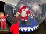 Rev. Dr. Leroy Barber visits with children as Santa Claus through a 10-foot-tall inflatable snow globe in Portland, Ore.