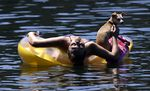 Justine Hicks floats with her dog, Kiana, on the Willamette River in Portland, Ore., Monday, July 6, 2015. People and their pets were out in droves in the river trying to keep cool from an extended heat wave with higher than normal temperatures for this time of year. (AP Photo/Don Ryan)
