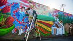 Muralist Hector H. Hernandez puts finishing touches on a mural on the side of the Woodburn Independent newspaper building in downtown Woodburn, Oregon.