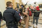 In this Jan. 6, 2021, file photo supporters of President Donald Trump are confronted by U.S. Capitol Police officers outside the Senate Chamber inside the Capitol in Washington. An Arizona man seen in photos and video of the mob wearing a fur hat with horns was also charged Saturday in Wednesday's chaos. Jacob Anthony Chansley, who also goes by the name Jake Angeli, was taken into custody Saturday, Jan. 9.