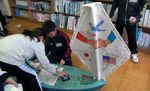 Students at Okuki Elementary in Japan finish sealing the hull on the ship American students built for them.
