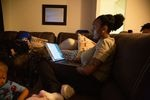 Monet Carter-Mixon sits with her sons while reading pre-law coursework at her University Park apartment in Seattle. Her brother's death has highlighted shortcomings in police reform efforts.