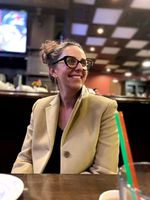 A person sitting at a bar or restaurant table smiles.