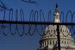 The Dome of the Capitol Building is visible through razor wire installed on top of fencing on Capitol Hill in Washington, Thursday, Jan. 14, 2021.