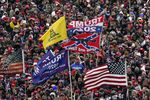Supporters listen as President Donald Trump speaks as a Confederate-themed and other flags flutter in the wind during a rally in Washington.