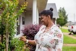 A person smiles as she looks at a shrub outside a house.