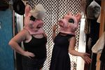 """Helen's Pacific Costumers Manager Sally Newman, right, and her roommate, left, model two of the """"Three Little Pigs"""" mascot heads."""