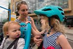 Annie Rudwick adjusts her daughter's helmet as they prepare for a bike ride.