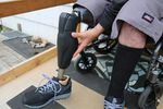 A close up photo shows just the lower body of a person in a wheel chair as they attach a prosthetic leg where there is otherwise no limb below their knee on one side.