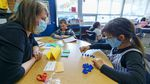 a teacher watches as a young girls sorts blue figurines while learning to count