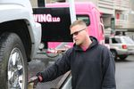 A person wearing sunglasses stands next to a tow truck which has a vehicle lifted onto its flat bed.