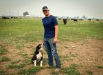 Justin Grant stands beside his border collie in his cow field in Midland on Aug. 5.