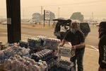 In this Sept. 8, 2020, file photo Jonathan Thompson of the Keizer, Ore., Chamber of Commerce delivers donated bottled water to the Oregon State Fairgrounds in Salem, which is now an evacuation center as wildfires threaten towns in Oregon.
