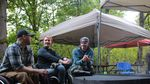 Three people sit together at a park picnic area. At least two of them are seated in wheelchairs.