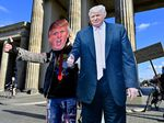 A supporter of President Trump poses with a cardboard cutout likeness in front of the Brandenburg Gate, in Berlin on Wednesday.