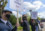 Justin Ringle, a grad student at the Oregon Institute of Technology, center, stands on the picket line in front of the Wilsonville campus, April 27, 2021.