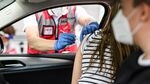 The passenger in a car receives an injection through her window, while the driver (who is wearing a mask) look on.