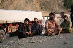 Razziq Mehmon (second from right) waits in Pakistan near the border to drive a truck loaded with cement bound for Jalalabad.
