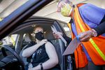 Annalisa Birt of Portland, left, prepares for her vaccination from Marlene Ikeda at a drive-thru mass COVID-19 vaccination clinic at Portland International Airport, April 9, 2021. The clinic is a joint operation hosted by Oregon Health & Science University, the Port of Portland and the American Red Cross.