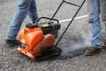 An ODOT maintenance crew uses a machine that tamps down asphalt after filling a pothole on Highway 26.